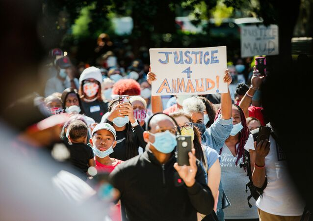 Supporters of the Georgia NAACP (National Association for the Advancement of Colored People) wearing protective masks protest after the death in February of Ahmaud Arbery, an unarmed young black man shot after being chased by a white former law enforcement officer and his son, at the Glynn County Courthouse in Brunswick, Georgia, U.S., May 8, 2020
