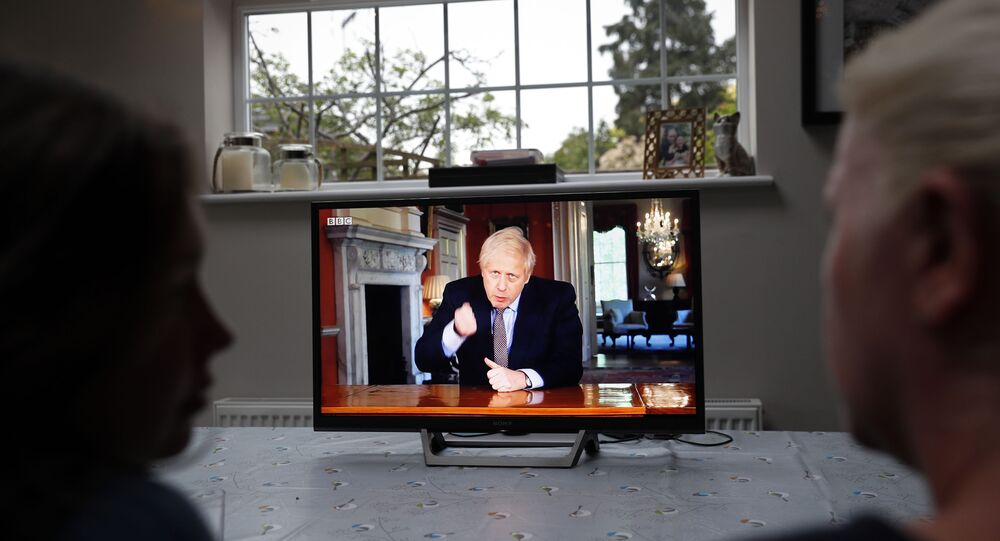 A family gather around the television to watch Britain's Prime Minister Boris Johnson give a televised message to the nation in Hartley Wintney, west of London on May 10, 2020, as the government sets out it's roadmap to ease the national lockdown due to the novel coronavirus COVID-19 pandemic.