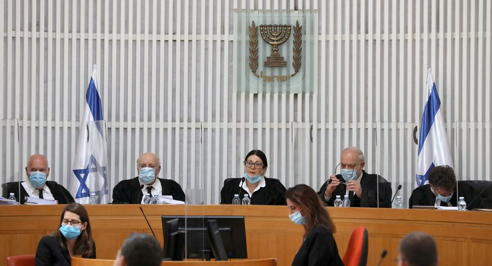 A panel of judges of the Israeli Supreme Court wear face masks as they address a discussion on a petition asking whether Israeli Prime Minister Benjamin Netanyahu can form a government legally and publicly when indictments are filed against him on a charges of fraud, bribery, and breach of trust, at the Israeli Supreme Court in Jerusalem 4 May 2020.
