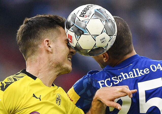 Dortmund's Julian Weigl and Schalke's Amine Harit challenge for the ball during the Bundesliga derby match in October 2019.