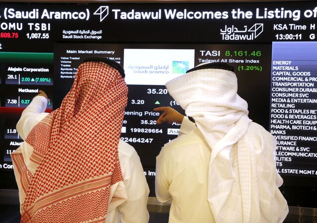 Saudi stock market officials watch the market screen displaying Saudi Arabia's state-owned oil company Aramco after the debut of Aramco's initial public offering (IPO) on the Riyadh's stock market in Riyadh, Saudi Arabia, Wednesday, Dec. 11, 2019