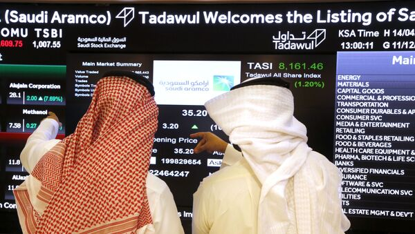 Saudi stock market officials watch the market screen displaying Saudi Arabia's state-owned oil company Aramco after the debut of Aramco's initial public offering (IPO) on the Riyadh's stock market in Riyadh, Saudi Arabia, Wednesday, Dec. 11, 2019 - Sputnik International