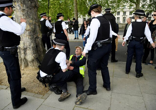 An anti lockdown protester is detained by police officers in London following the outbreak of the coronavirus disease (COVID-19), London, Britain, May 2, 2020. REUTERS/Toby Melville REFILE - CORRECTING CAPTION