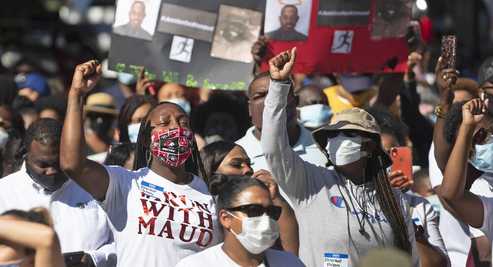 People react during a rally to protest the shooting of an unarmed black man, Friday, May 8, 2020, in Brunswick Ga. Two men have been charged with murder in the February shooting death of Ahmaud Arbery, whom they had pursued in a truck after spotting him running in their neighborhood.