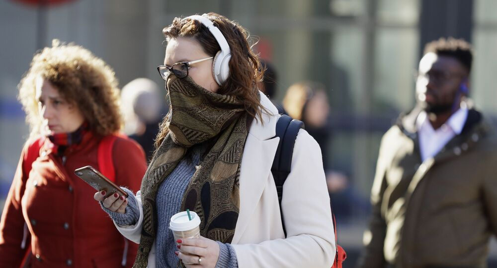 A commuter covers her face in London, Monday, March 16, 2020. For most people, the new coronavirus causes only mild or moderate symptoms, such as fever and cough. For some, especially older adults and people with existing health problems, it can cause more severe illness, including pneumonia.