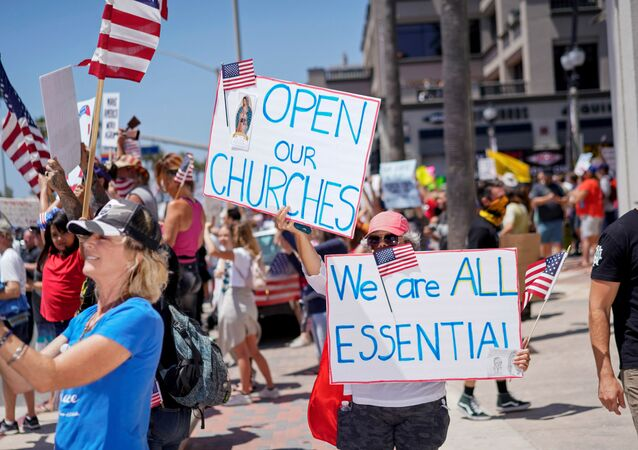People gather near Huntington Beach Pier to protest Gov. Gavin Newsom?s order to temporarily close state and local beaches in Orange County, during the outbreak of the coronavirus disease (COVID-19), in Huntington Beach, California, U.S., May 1, 2020