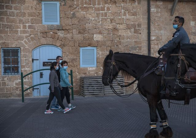 People wear protective face masks amid concerns over the country's coronavirus outbreak as they walk in the city of Jaffa, near Tel Aviv, Israel, 9 May 2020. Israeli authorities have recently begun loosening the restrictions of the coronavirus lockdown, the easing has brought people out of their homes to enjoy the outdoors.