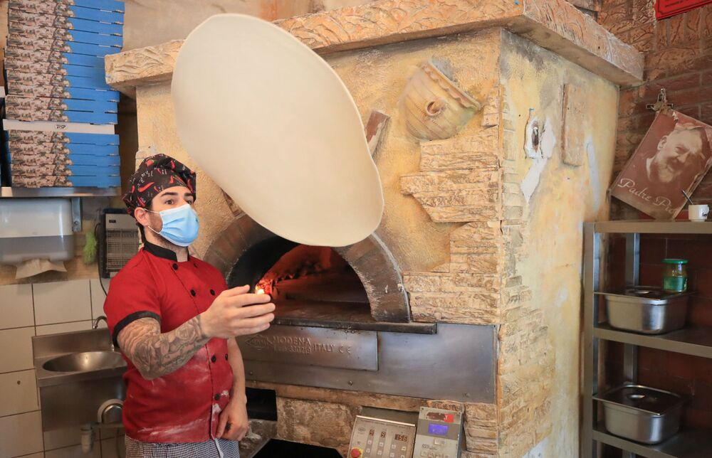 Pizza chef Carmelo la Ciura prepares food in the restaurant Tuscolo that reopened today, following weeks of closure due to the global outbreak of the coronavirus disease (COVID-19), in Bonn, Germany, 11 May 2020.