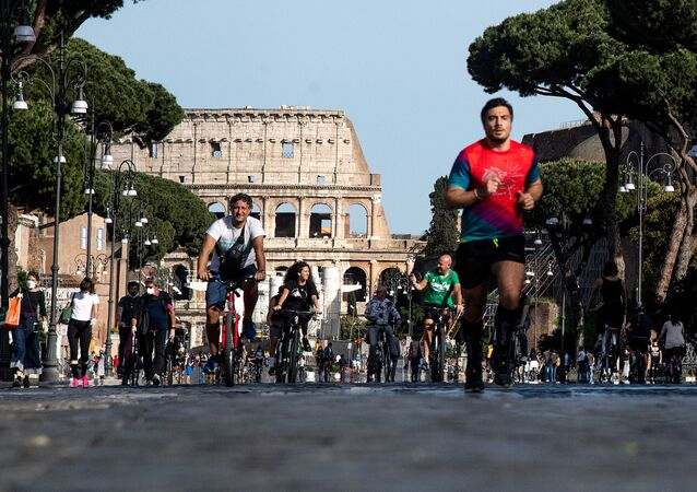 People jog or ride along Via dei Fori Imperiali in central Rome on May 10, 2020 during the country's partial lockdown aimed at curbing the spread of the COVID-19 infection, caused by the novel coronavirus.