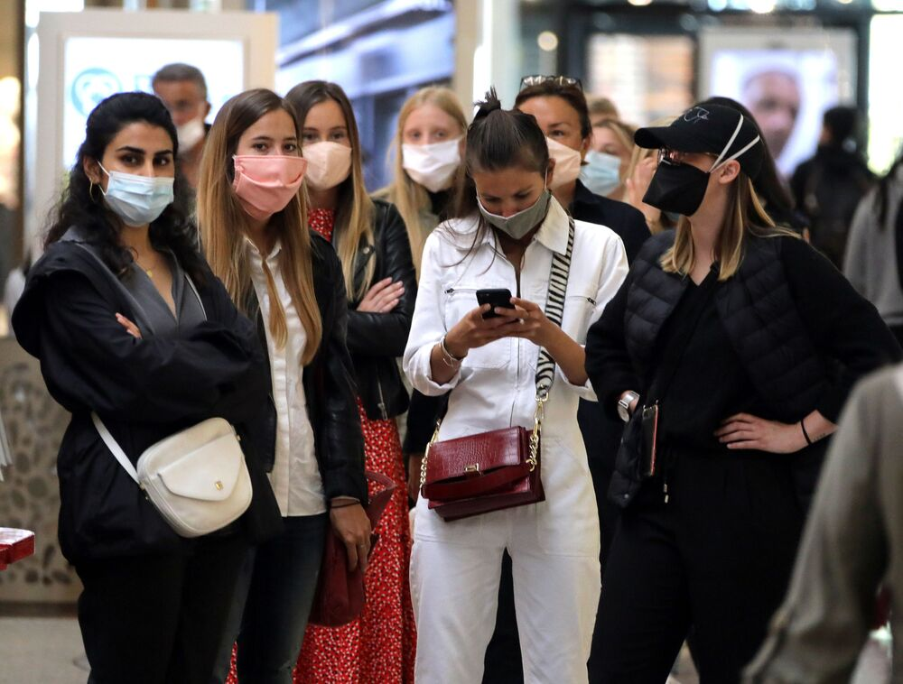 People wearing protective face masks wait to enter a Cap 3000 department store in Saint Laurent du Var near Nice as France softens its strict lockdown rules during the outbreak of the coronavirus disease (COVID-19) in France, May 2020.