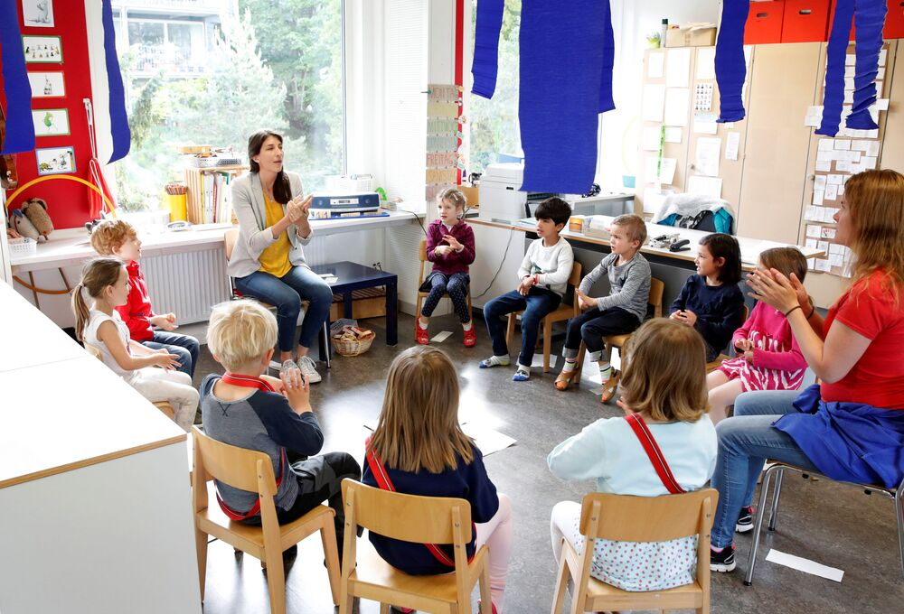 Children listen to the explanations of teacher Angela Melad on how to wash their hands at the KiGa Hutten kindergarten during the first day back as Switzerland eases the lockdown measures during the coronavirus disease (COVID-19) outbreak in Zurich, Switzerland 11 May 2020.