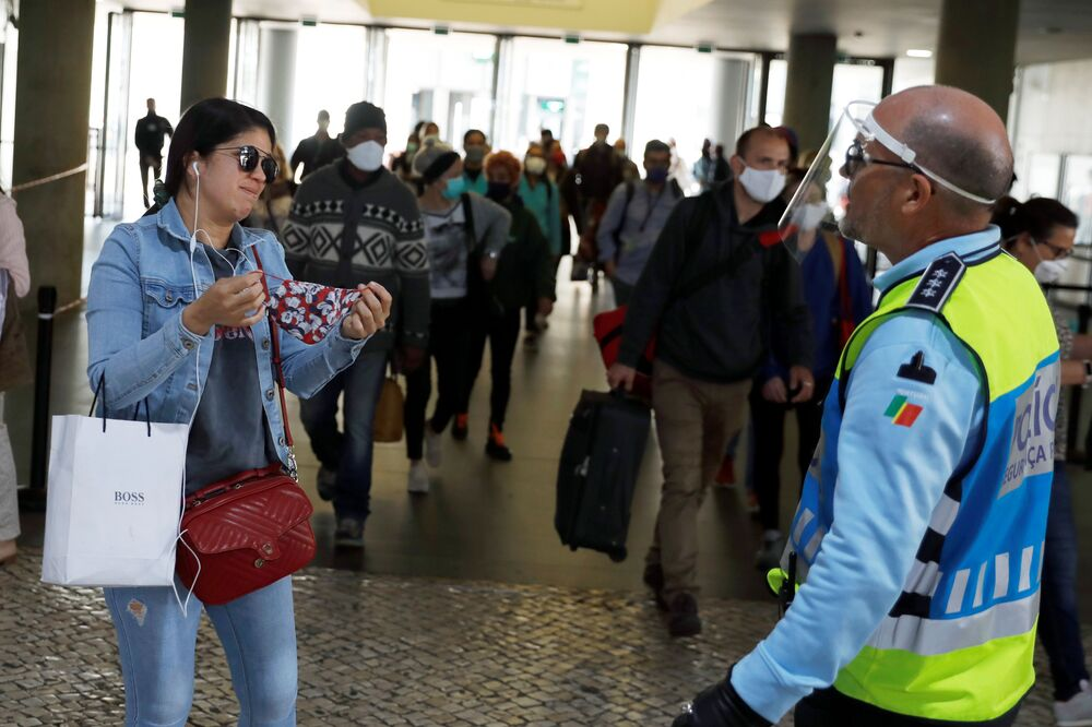 A police officer asks a woman to put on her protective mask, as the country eases the lockdown due to the spread of the coronavirus disease (COVID-19), at Cais do Sodre station in Lisbon, Portugal 4 May 2020.