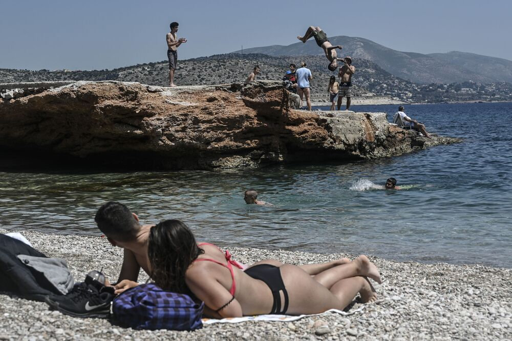 Sunbathers watch a young man doing a backflip into the water as they lie on the beach in Athen's southern suburb on 9 May 2020, as the nations readies for the reopening of schools and most of shops starting 11 May.