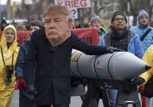An anti-war protester wears a mask showing US President Donald Trump in Berlin, Germany, Saturday, Nov. 18, 2017 during a demonstration  against nuclear weapons near the Brandenburg Gate