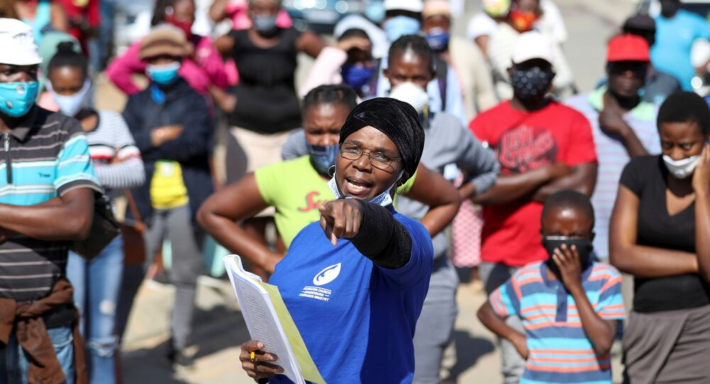 A woman gestures as she holds a book with names of recipients during food distribution, as South Africa starts to relax some aspects of a stringent nationwide coronavirus disease (COVID-19) lockdown, in Diepsloot near Johannesburg, South Africa, May 8, 2020