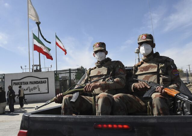 Pakistani soldiers wearing facemasks patrol near the closed Pakistan-Iran border in Taftan on February 25, 2020 as fears over the spread of the COVID-19 coronavirus escalate following an outbreak in neighbouring Iran