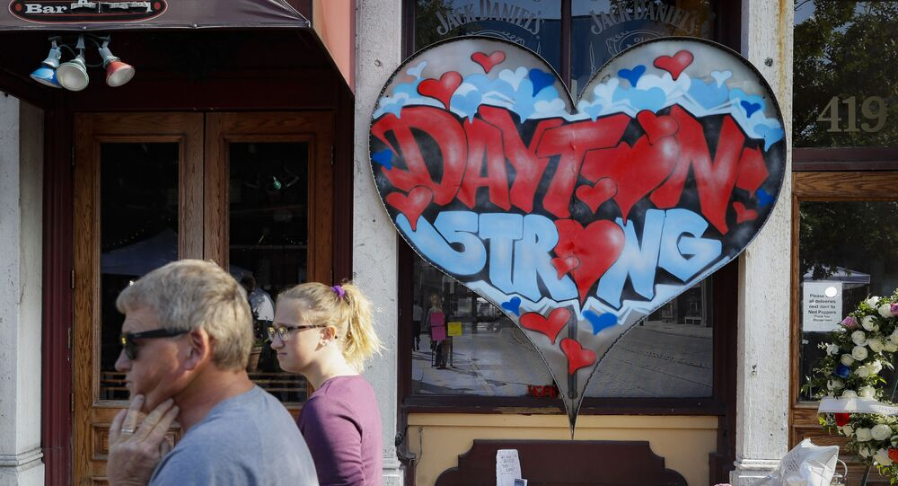 People walk past a makeshift memorial for the slain and injured victims of a mass shooting in Dayton, Ohio in August 2019.