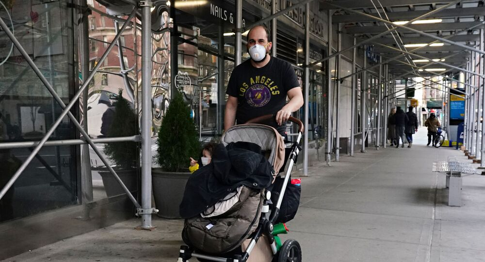 A man wearing a protective mask pushes a child wearing a protective mask in a stroller during the coronavirus pandemic on April 12, 2020 in New York City.