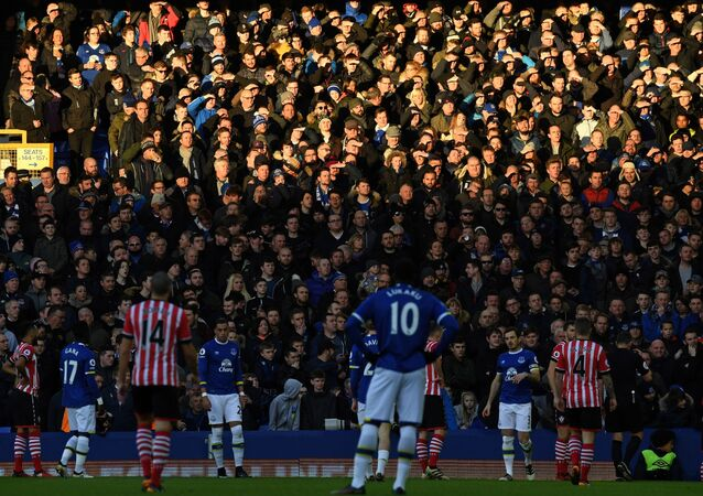 n this file photo taken on January 02, 2017 Fans shield their eyes from the Sun during the English Premier League football match between Everton and Southampton at Goodison Park in Liverpool, north west England.