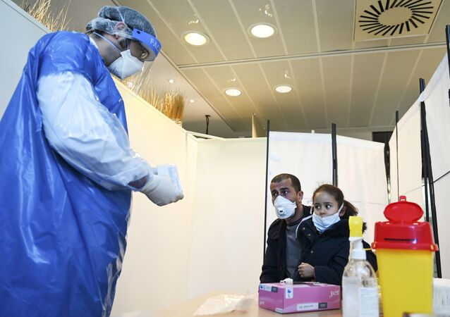 A medical staff member wearing protective facemask and suit, and a face-shield, prepares to collect from a man and his daughter at a COVID-19 testing centre set up in the European Parliament on May 12, 2020