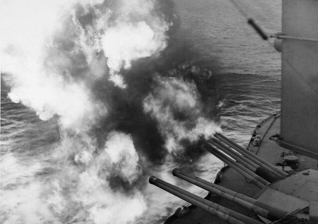 Mushrooms of smoke and flame billow out from the giant USS Nevada as the battleship provides artillery support for Allied ground forces in France by hammering enemy installations from her vantage point in the English Channel, June 6, 1944. (AP Photo)