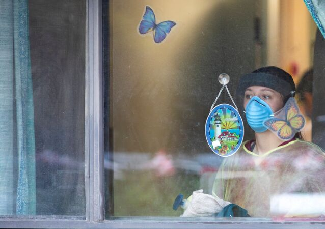 A worker looks out after police officers placed butterfly stickers on windows at Orchard Villa Retirement Residence on Mother's Day, after several residents died of the coronavirus disease (COVID-19) in Pickering, Ontario, Canada May 10, 2020