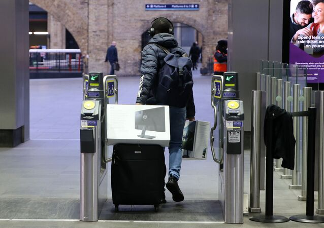 A man carries computer screens and equipment as he pulls a suitcase through the ticket barriers at King's Cross train station in central London, on March 19, 2020, as the coronavirus pandemic continues