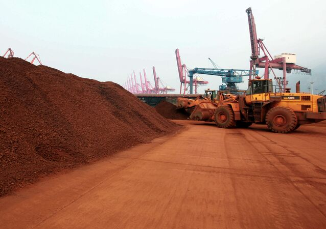 In a picture taken on September 5, 2010 a man driving a front loader shifts soil containing rare earth minerals to be loaded at a port in Lianyungang, east China's Jiangsu province, for export to Japan