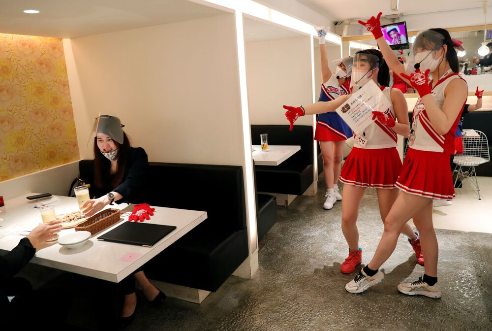 Waitresses in cheerleader costumes with visitors at the Cheers One restaurant in Tokyo