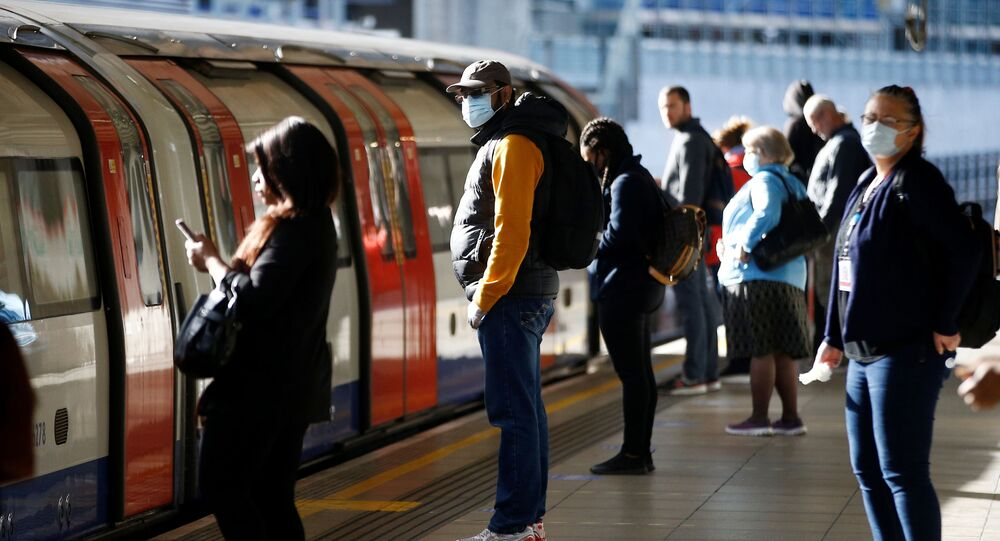 Commuters, some wearing masks are seen at Canning Town station, following the outbreak of the coronavirus disease (COVID-19), London, Britain, May 13, 2020.