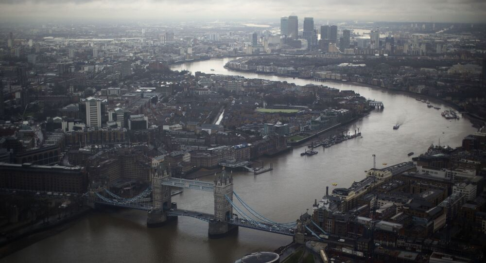 Tower Bridge, centre, and the Canary Wharf business district in the distance as the River Thames flows through London, are seen through a window during the official opening of The View viewing platform at the 95-storey Shard skyscraper in London, Friday, Feb. 1, 2013