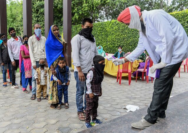 A health worker checks the body temperature of migrant workers before they go to Amritsar railway station to take a special train to Ambedkar Nagar in Uttar Pradesh state back to their hometowns after the government eased a nationwide lockdown imposed as a preventive measure against the COVID-19 coronavirus,on the outskirts of  Amritsar on May 13, 2020