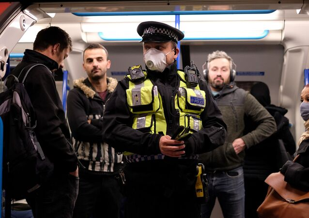 A police officer wearing PPE (personal protective equipment), including a face mask as a precautionary measure against COVID-19, stands with commuters as they travel in the morning rush hour on TfL (Transport for London) London underground Victoria Line trains from Finsbury Park towards central London on May 13, 2020