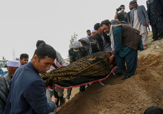 Mourners carry a covered dead body during a burial ceremony following a suicide attack in a maternity hospital, at a cemetery in Kabul on May 13, 2020.