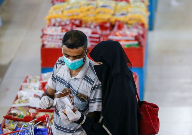 A couple wearing protective face masks and gloves shop at a supermarket amid concerns of the spread of the coronavirus disease (COVID-19), in Sanaa, Yemen May 11, 2020.