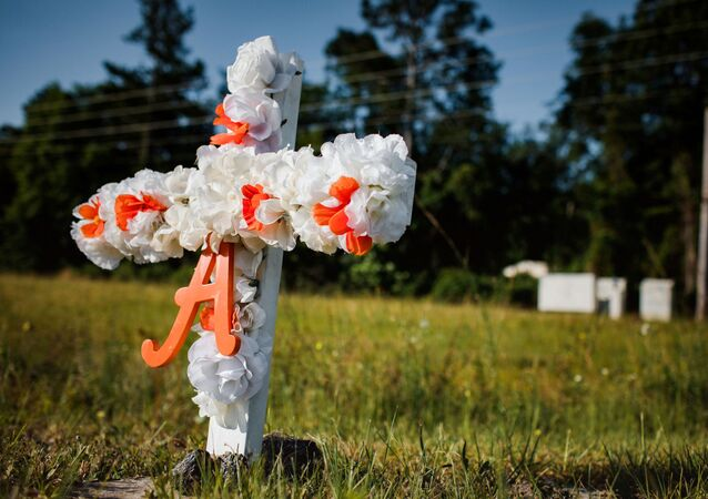 A white and orange cross with an A on it stands stuck in the ground along highway 17 at the entrance of the Satilla Shores neighbourhood where Ahmaud Arbery, an unarmed young black man, was shot after being chased by a white former law enforcement officer and his son, at the Glynn County Courthouse in Brunswick, Georgia, U.S., May 8, 2020