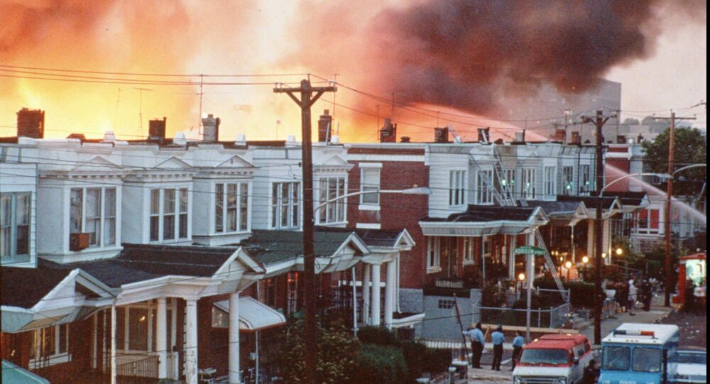 FILE--Row houses in Philadelphia burn after officials dropped a bomb on the MOVE house in this May 1985 photo from files. Ramona Africa, the lone adult survivor of the May 13, 1985 fire, and two other MOVE members sued the city of Philadelphia, and the former police and fire commissioners for financial damages in what was the first trial in court to address the MOVE bombing. The jury said Monday afternoon June 24, 1996, that it reached a verdict, but the result was not announced immediately.(AP Photo/files)