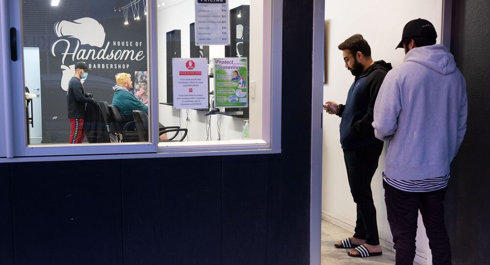 People queue for a haircut at a barber shop in Wellington on May 14, 2020. New Zealand will phase out its coronavirus lockdown over the next 10 days after successfully containing the virus, although some restrictions will remain, Prime Minister Jacinda Ardern announced on May 11.