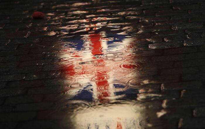 The Union flag is reflected in a puddle during an event called Brussels calling to celebrate the friendship between Belgium and Britain at the Grand Place in Brussels, Thursday, Jan. 30, 2020