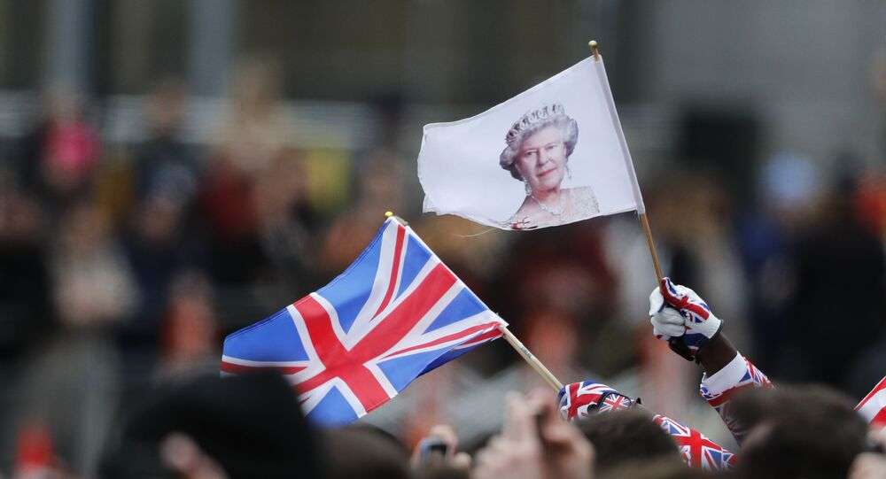 People wave a British union flag and a flag bearing the image of Britain's Queen Elizabeth II ahead of the annual Commonwealth Day service at Westminster Abbey in London, Monday, March 9, 2020