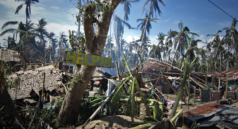 Destroyed houses and trees with a slogan calling for help are seen along a road in the village of Mantang, Taft town Eastern samar province central Philippines on December 8, 2014, a day after typhoon Hagupit hit the province