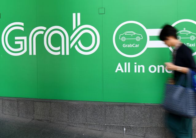 A woman walks past the Grab transport office in Singapore on September 24, 2018