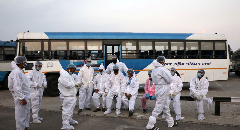 Bus drivers wearing protective gear wait for people that arrived from the southern state of Tamil Nadu after a limited reopening of India's giant rail network following a nearly seven-week lockdown to slow the spreading of the coronavirus disease (COVID-19), at the Howrah Junction railway station on the outskirts of Kolkata, India, May 12, 2020. REUTERS/Rupak De Chowdhuri