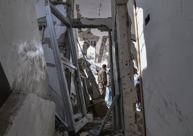 In this photo released by the Syrian official news agency SANA, people look at the rubble of a house that according to the Syrian authorities was attacked by an Israeli airstrike, in the Damascus suburbs of Hajira, Syria, Monday, April 27, 2020