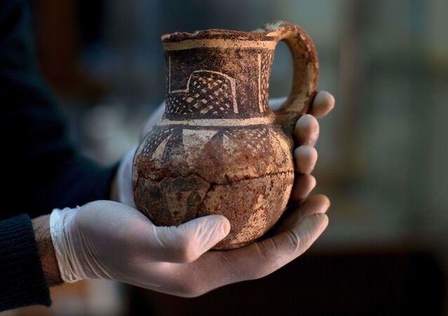 In this Tuesday, Feb. 23, 2016 photo, Jihad Abu Kahrlah, an archeologist at Syria's National Museum, holds an artifact delivered from the Daraa Museum to Damascus, Syria