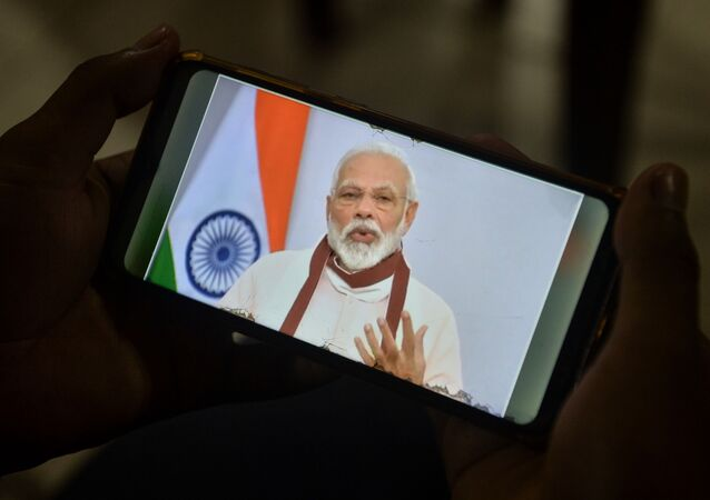 A youth watches Indian Prime Minister Narendra Modi's address to the nation on his mobile phone during a government-imposed nationwide lockdown as a preventive measure against the COVID-19 coronavirus, in Siliguri on 12 May 2020.