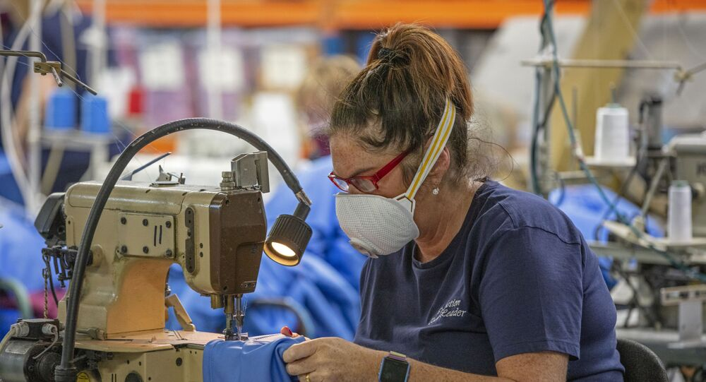 A worker wears a protective face mask as she makes scrubs for front-line National Health Service (NHS) staff in O'Neills sportswear factory in Strabane in Northern Ireland on March 26, 2020.