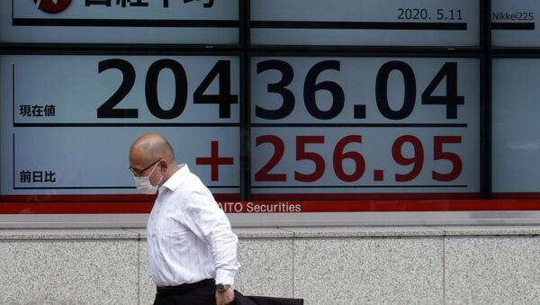 A man wearing a face mask  walks past an electronic stock board showing Japan's Nikkei 225 index at a securities firm in Tokyo Monday, May 11, 2020 - Sputnik International