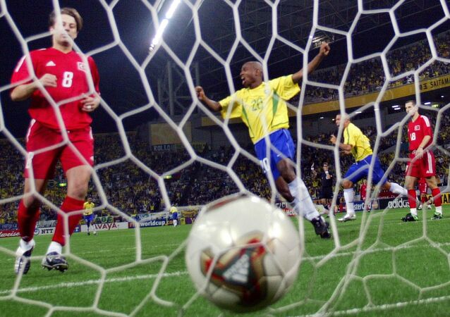 The ball goes into the net as Brazil's forward Edilson (20) and  forward Ronaldo (2nd-L) celebrate during  the Brazil-Turkey semi-final match of the FIFA 2002 World Cup Korea Japan 26 June, 2002, in Saitama, Japan