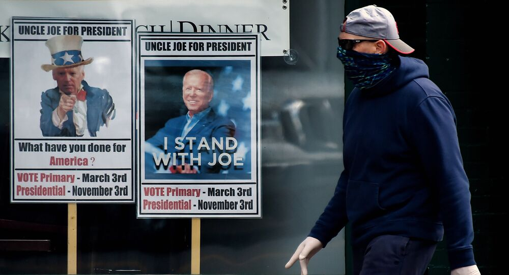 A man wearing a face mask walks past signs for Joe Biden's 2020 presidential campaign amid the coronavirus outbreak on May 11, 2020 in Alexandria, Virginia